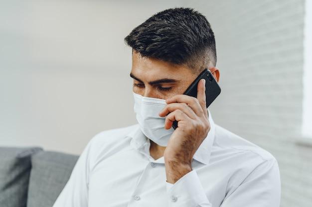Красивый молодой бизнесмен с маской для лица разговаривает по телефону