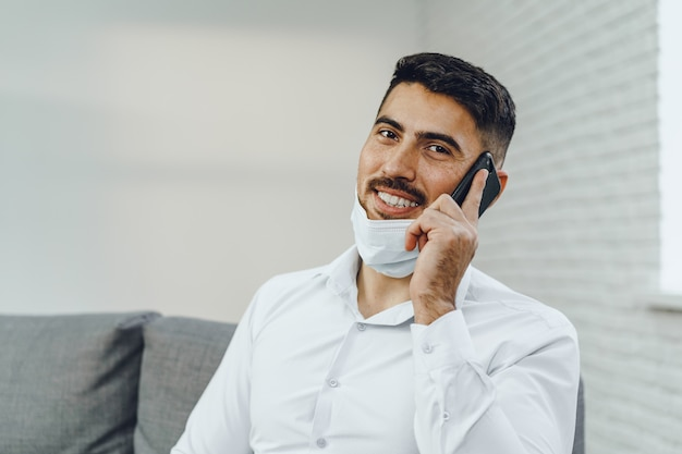 Handsome young businessman with face mask talking on the phone