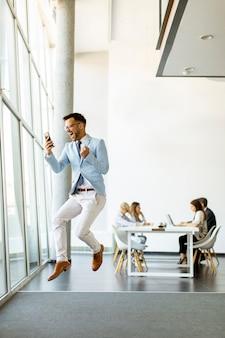 Красивый молодой бизнесмен со смартфоном в современном офисе прыгает после получения отличной новости