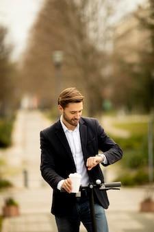 コーヒーカップを持ち帰り、電動スクーターで時間をチェックするハンサムな青年実業家