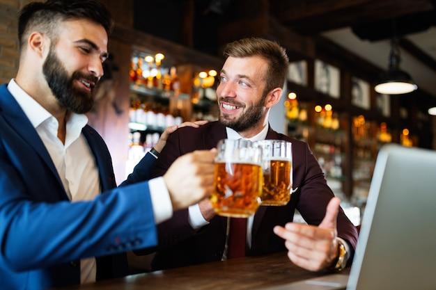 パブで休んでいる間、ビールを飲み、話し、笑顔のハンサムな若いビジネスマン