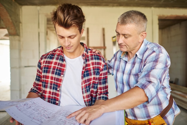経験豊富な男性と一緒に働くハンサムな若い大工