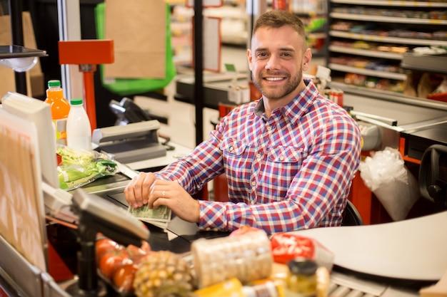 Красивый молодой кассир работает в супермаркете