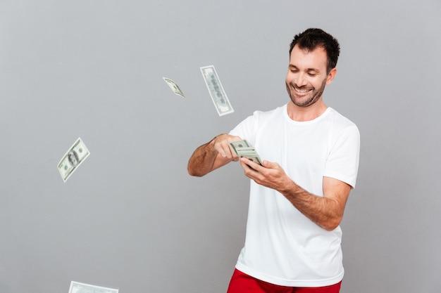 Красивый молодой случайный человек, считающий деньги на сером фоне