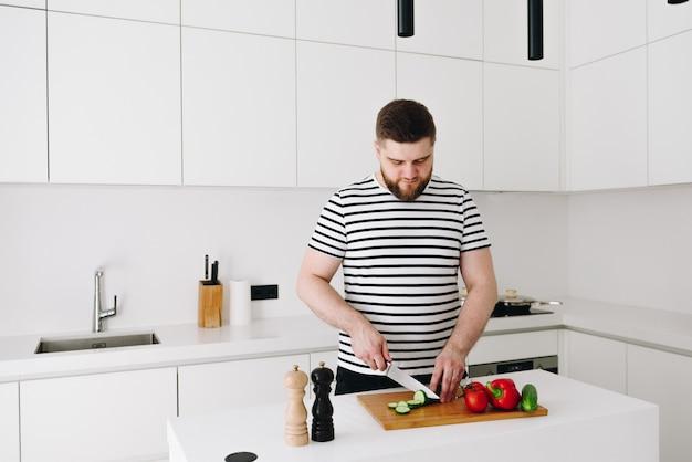 ハンサムな若い白人男性がモダンな明るい白いキッチンで素敵な健康的な野菜の食事やサラダを調理