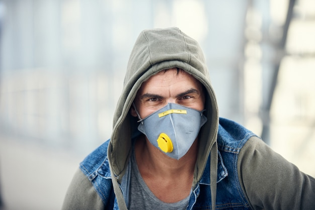 Handsome young caucasian man in hoody on the street with a medical face mask on.