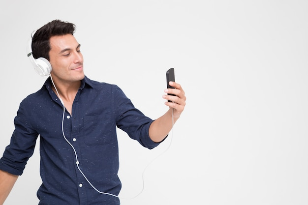 Handsome young caucasian man listening music with headphones on smartphone