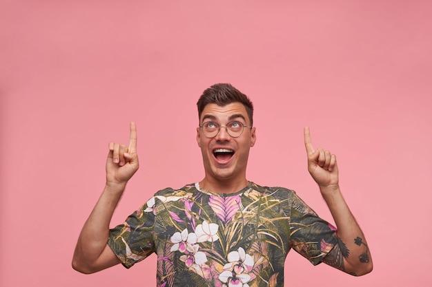 Красивый молодой очаровательный мужчина в цветочной футболке с короткой стрижкой стоит, подняв указательные пальцы и радостно глядя вверх