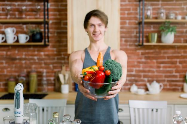 キッチンで木製のテーブルの近くに立って、健康的な野菜と果物のボウルを保持しているスポーツ服でハンサムな若い陽気な男。健康とビーガンフードのコンセプト