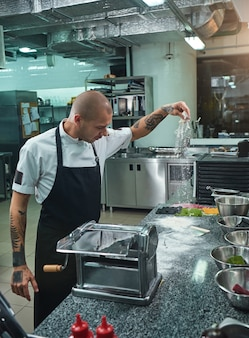 Handsome young chef with black tattoos on his arms pouring flour on kitchen table