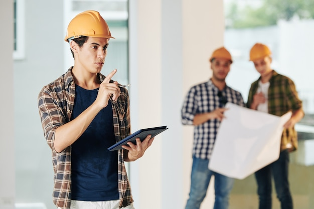 Handsome young civil engineer in hardhat and plaid shirt inspecting construction site and taking notes in document on tablet computer