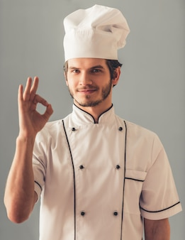 Handsome young cook in uniform is showing ok sign.