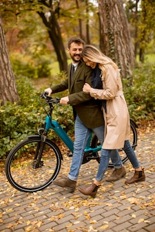 Handsome young couple in the autumn park with electrical bicycle