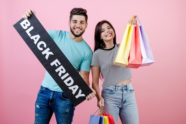 Handsome young couple boyfriend and girlfriend with black friday sign and colorful shopping bags