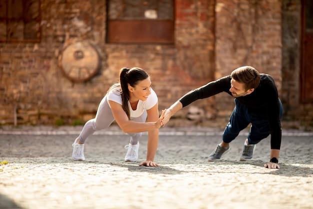 잘 생긴 젊은 부부는 도시 환경에서 한 팔 팔 굽혀 펴기 운동을 doung
