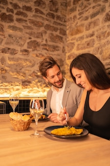 Handsome young couple in love in a restaurant, having fun having dinner together, celebrating valentine's day