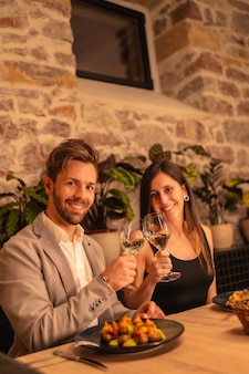 A handsome young couple in love in a restaurant, toasting glasses of wine, celebrating valentine's day, vertical photo