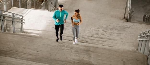 都市環境で走っているハンサムな若いカップル
