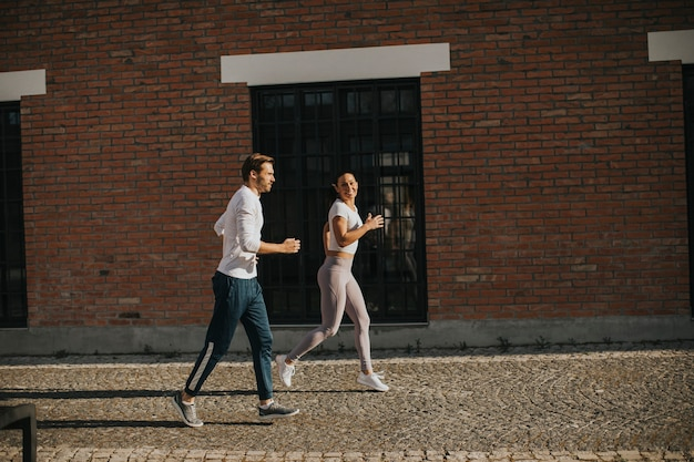 都市環境で実行されているハンサムな若いカップル