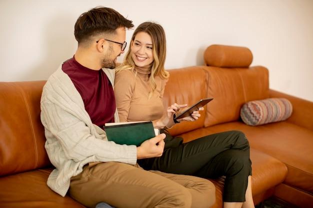 Красивая молодая пара вместе с помощью цифрового планшета, сидя на диване у себя дома