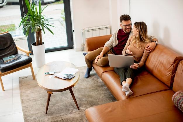Красивая молодая пара, используя ноутбук вместе, сидя на диване у себя дома