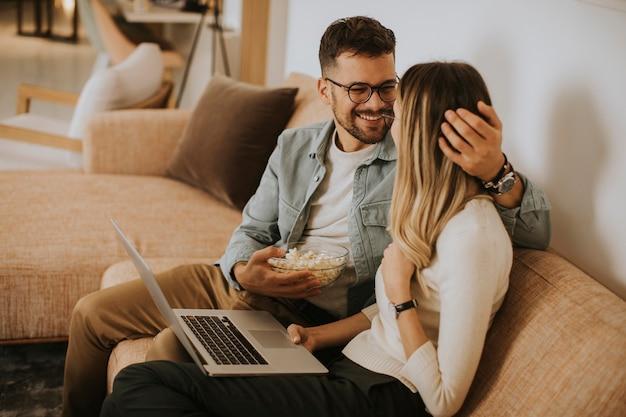 Красивая молодая пара, используя ноутбук вместе, сидя на диване у себя дома Premium Фотографии