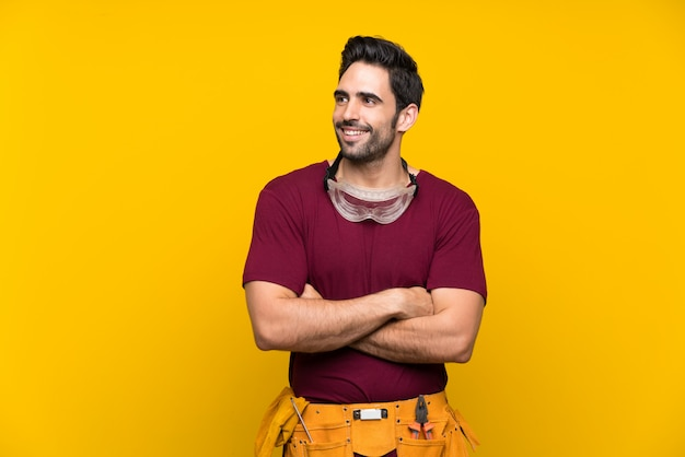 Handsome young craftsman over isolated yellow background looking up while smiling