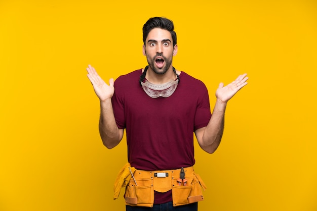 Handsome young craftsman over isolated yellow background with shocked facial expression