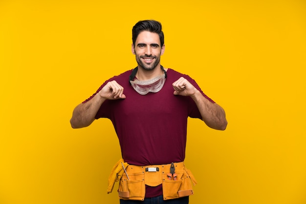 Handsome young craftsman over isolated yellow wall proud and self satisfied