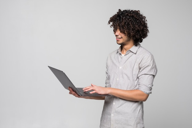 Handsome young curly haired man working on laptop computer standing of isolated on white wall,