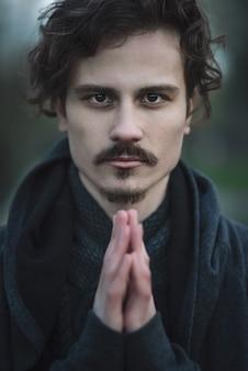 Красивый молодой кудрявый мужчина испытывает глубокие религиозные чувства.