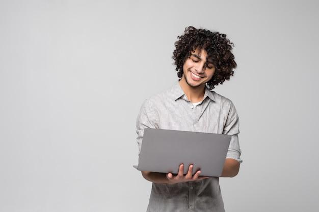 白い壁に分離されたラップトップコンピューターで立っているハンサムな若い巻き毛男