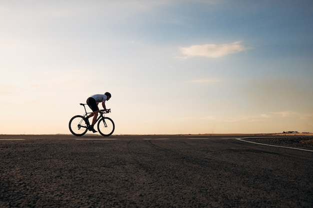 Handsome young cyclist wearing sport clothing and protective helmet biking on road during evening time