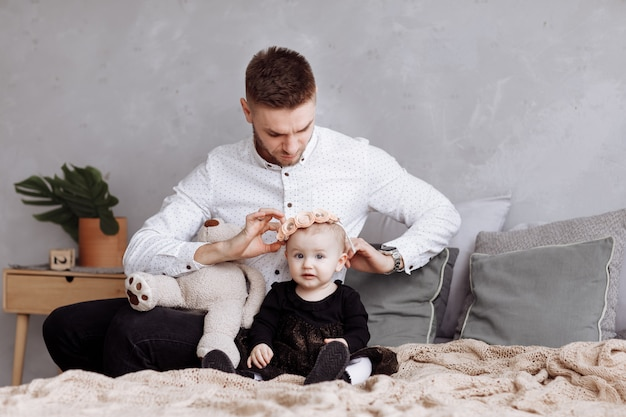 Handsome young dad and his cute baby girl are sitting and playing with teddy bear on bed at home. father's, baby's day. family spending time together