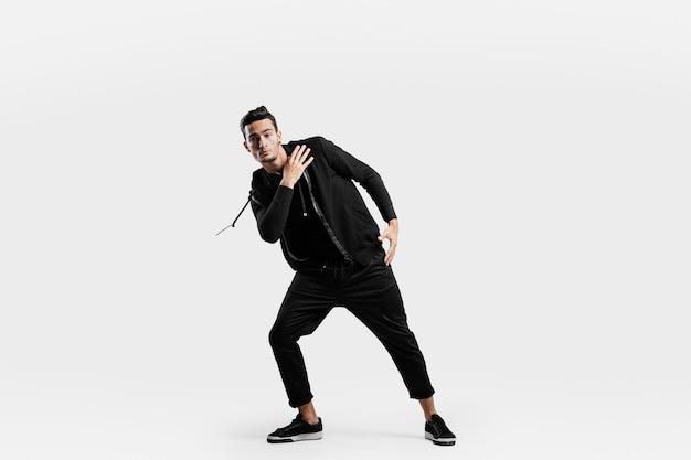 スポーツの黒い服を着たハンサムな若いダンサーがストリートダンスを踊っています