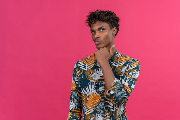 Handsome young dark skin man weighing opportunities standing in thoughtful pose with fist on chin raising eyebrow looking at upper right corner