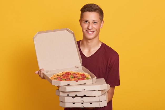 Handsome young delivery worker holding stack of pizza boxes, dressed casual t shirt, looking at camera and smiling, showing open box with tasty pepperoni, posing isolated on yellow studio