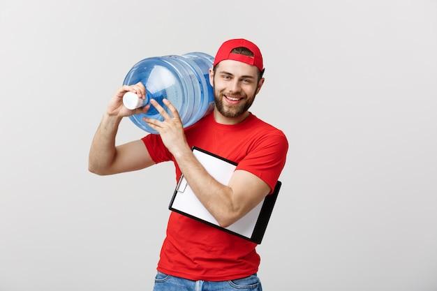Красивый молодой работник доставки в красной форме держит бутылку воды