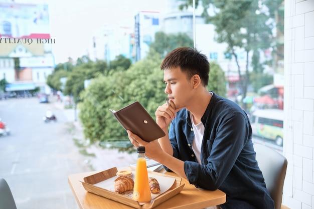 Красивый молодой дизайнер пишет творческие графические заметки и делает эскиз в записной книжке, сидя за деревянным столом в интерьере кофе. вдумчивый человек пишет новые успешные идеи для статьи в блоге