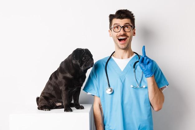 Красивый молодой врач в ветеринарной клинике указывая пальцем вверх и выглядел пораженным, стоя рядом с милой черной собакой мопса, на белом фоне.