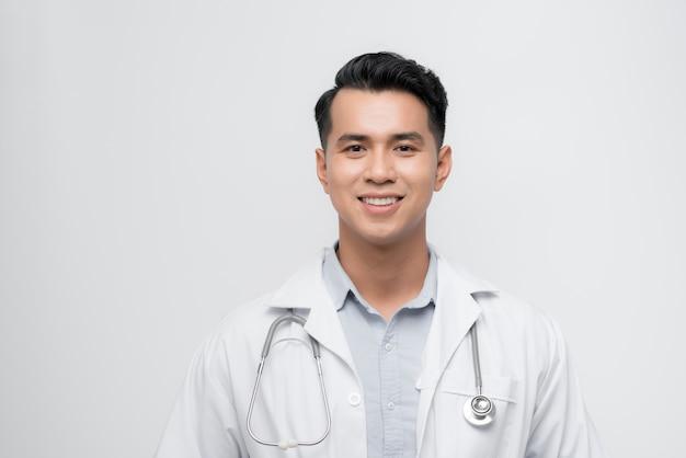 ハンサムな若い医者の男は、笑顔で横を見て、考えて見つめています。