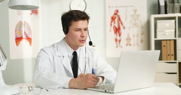 A handsome young doctor with headset in front of her laptop, talking with a patient.
