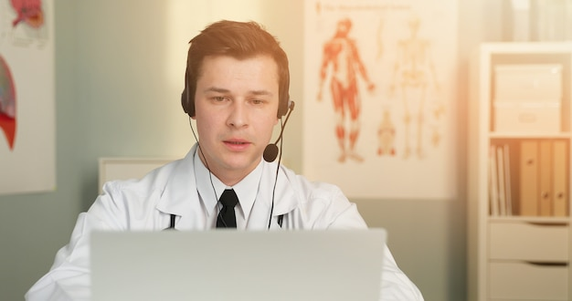 A handsome young doctor with headset gives online consultation using laptop