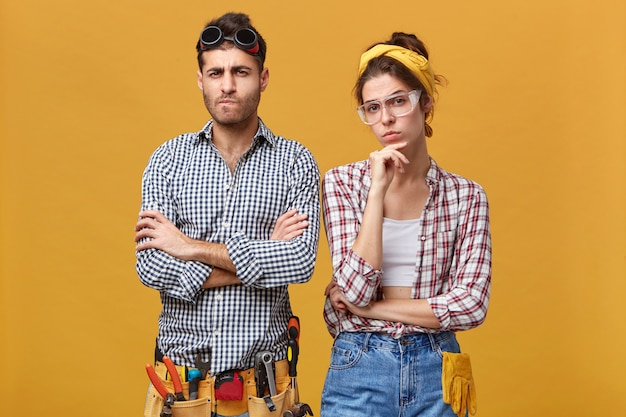 Handsome young electrician wearing belt kit with plier, flexible ruler, wrench, screwdriver and hammer folding arms, standing next to his female colleague, both having skeptic and distrustful looks