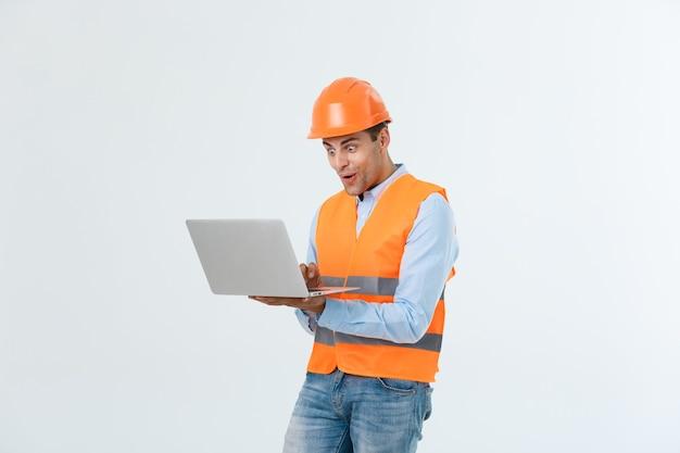 Bel giovane ingegnere uomo su grigio che indossa il casco di sicurezza con faccia sorpresa scioccata.