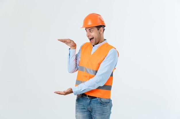 ショックを受けた驚きの顔と安全ヘルメットを身に着けている灰色のハンサムな若いエンジニアの男。