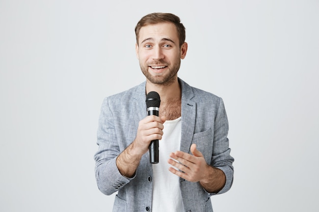 Handsome young entertainer with microphone, giving speech