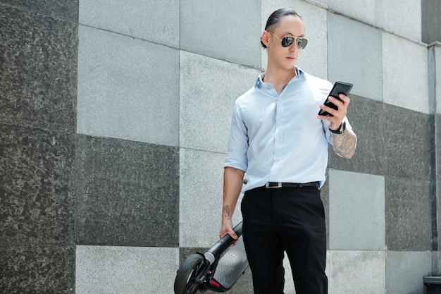 電動スクーターとスマートフォンでテキストメッセージを読んで屋外に立っているサングラスのハンサムな若い起業家