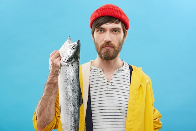 Handsome young european fisherman with beard showing his catch after fishing excursion. confident male wearing sailor shirt, raincoat and hat posing in with big sea fish