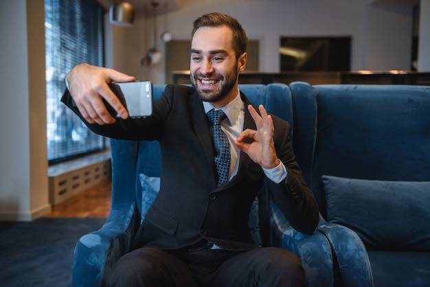 Красивый молодой взволнованный бизнесмен в костюме, сидя в холле отеля, используя мобильный телефон, принимая селфи, хорошо